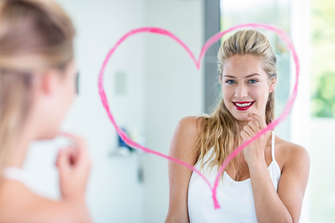 Woman with lipstick looking in the mirror